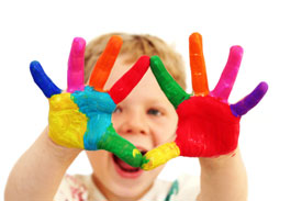 Five year old boy with hands painted in colourful paints ready for hand prints (istockphoto.com)